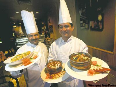 Samosa Crown chefs Sunil Komar (left) and Shailendra Rawat pose with, from left, Kashmiri aloo, dal makhani (black lentils) and goat curry.