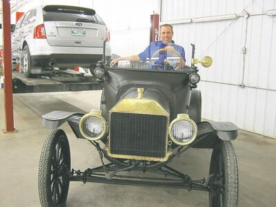 Metcalfe Garage president Neil Metcalfe seated in 1915 Model T Ford.