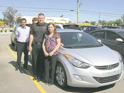 From left to right, Birchwood Hyundai sales rep Ervin Urizar, new sales manager Shannon Vezey, general sales manager David Cummins, new sales rep Aleks Baptista alongside hot-selling new 2013 Elantra.