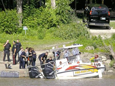 TREVOR HAGAN / WINNIPEG FREE PRESS Emergency personnel move a body from the Red River to the riverbank near Waterfront Drive on Saturday morning.