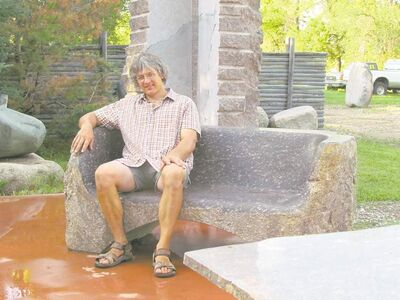 Local stone carver Todd Braun relaxes on a granite bench that has been smoothly polished.