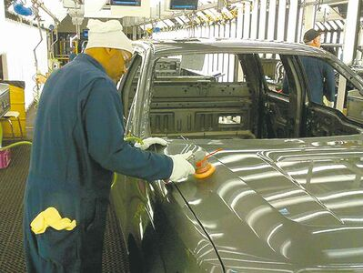 Ford Dearborn Truck Plant employee finishes any paint imperfections spotted by the automaker�s new Dirt Detection technology.