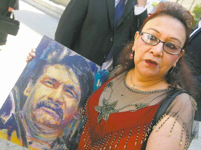 Esther Grant holds a painting of her brother, Brian Sinclair, outside the courtroom where an inquest into his death began in August.
