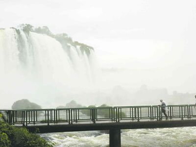 A tourist walks on a footbridge near the Iguazu Falls on the Brazilian side.