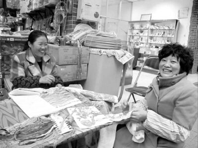 Women do needlework while waiting for customers at a plumbing supply store in Chengdu.