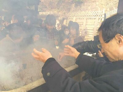 Visitors fan themselves with scented smoke from incense burned near the fire god shrine at the Kiyoshikojin Seicho-ji temple complex north of Osaka, Japan. Top right, tai-yaki is a sweet azuki bean-filled pancake in the shape of sea bream fish.