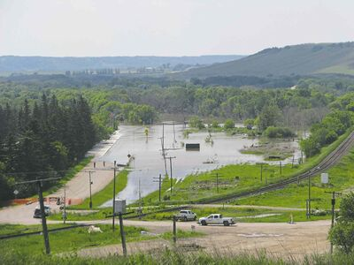 Water from the Qu'Appelle River flows over Highway 41 in St. Lazare Tuesday. Nine homes outside the community's ring dike were damaged.