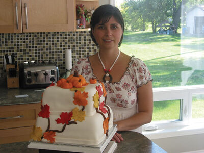 Melanie Mosset shows off a double-layer cake she's decorated with a fall theme.