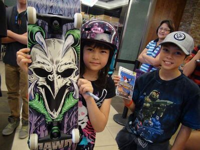 Jade (left) and Kyle Leesavage show off Tony Hawk merchandise they're hoping to get signed as they wait in line to meet the skateboarding star, who was in Winnipeg for a skateboarding demonstration Monday outside Sport Chek at Polo Park.