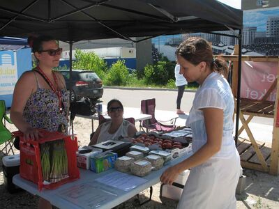 North End Food Security Network's Jasmine Tara and Melissa McDonald (centre)  and Main Street Farmers' Market  customer Sharon Johnson.