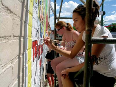 Sheena (front) and Vicki of Marymound work on The Guess Who mural at 1400 Main Street.