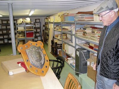 Rudy Friesen displays a shield that was awarded annually to the local school whose students won an athletic competition in the 1930s.