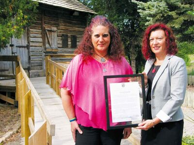 Sandra Horyski (left) and MLA Sharon Blady (Kirkfield Park) stand in front of Cuthbert Grant's Old Mill in St. James. Blady presented Horyski with a framed copy of the Member's Statement she read in the Manitoba legislature on Sept. 9 to recognize Horyski's work in raising money for a memorial marker for Grant.