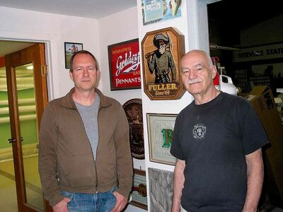 Left) Matthew Friesen and his father John Henry Friesen stand next to some of the signs that have been designed and made by their company, John Henry Creations.