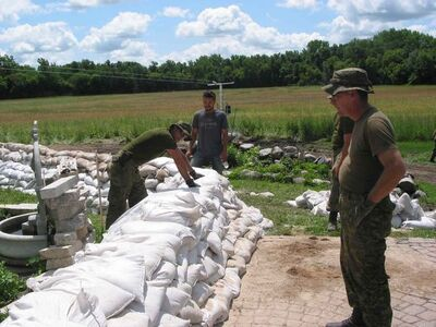 Members of the Second Battalion of Princess Patricia's Canadian Light Infantry help to raise the sandbag dike surrounding Gloria and Keven Van Camp's home on July 8.