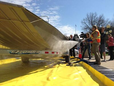 Aquatic Invasive Species Inspector Cori Kulbaba sprays a boat in demonstration of project outside the Manitoba Legislative Building on Wednesday.