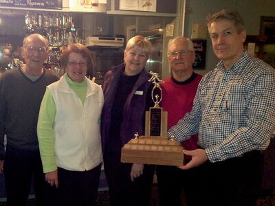 The Funspiel winning team of Neil Pineau (from left), Velma Davis, Judy Smith and Gil Dambly are presented with their trophy by Bruce Popham.