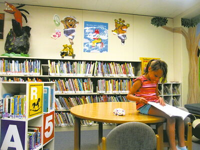 A young Transcona resident enjoys a good book in the children's department of the Transcona Public Library.