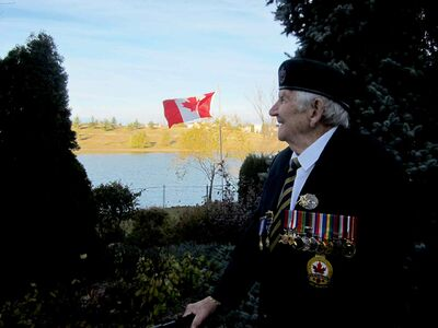Paul Martin, a 93-year-old veteran of the Second World War, looks out over his back yard, where a brand new Canadian flag flies, thanks to MP Lawrence Toet.