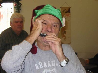 Gary Hyde plays his harmonica to celebrate a customer's birthday, a custom at the Little Corner Bakeshop.