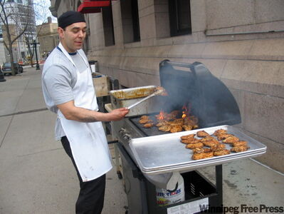 Street vendor barbecues sumptuous chicken on the streets of St. Paul.