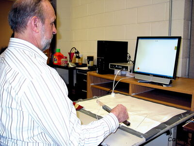 Dr. Tony Szturm tests arthritis research software using a pair of salad tongs.