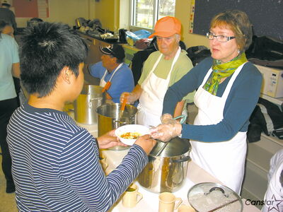 Volunteers serve up helpings of homemade chicken soup to students at  Archwood School.