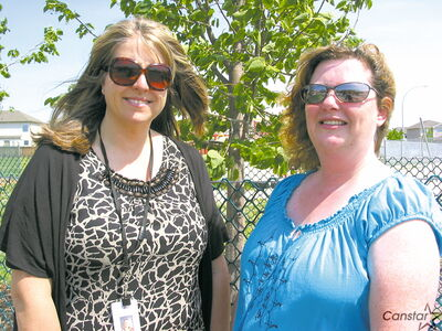 ILCS principal Darcy Cormack (left) and Faith Roper, chair of the school's playground committee, stand near a newly-planted tree at the school last year.