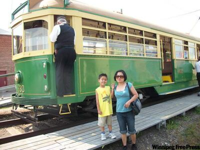 Edmonton streetcar that gives tourists a ride across the North Saskatchewan River over the High Level Bridge. Rose Lockert and son James, 6, pose in front of streetcar.