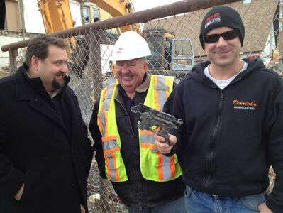 Scott Sime and Wayne Imrie look on as Ward Imrie shows gun found broken in the rubble.