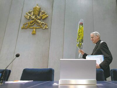 Vatican spokesman father Federico Lombardi holds a bunch of flowers as he arrives for a meeting at the Vatican Friday.