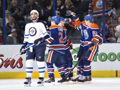 Winnipeg Jets' Dustin Byfuglien (33) looks on as Edmonton Oilers' Andrew Ference (21), Jordan Eberle (14) and Ales Hemsky (83) celebrate a goal during first period NHL hockey action in Edmonton, Alta., on Monday.
