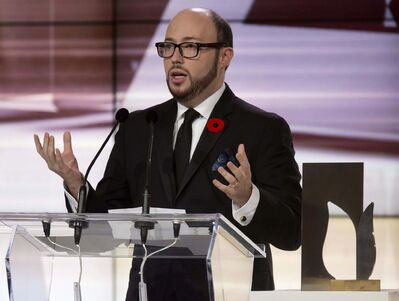 Sean Michaels accepts the Giller Prize for his book, Us Conductors, at a 2014 awards ceremony in Toronto. (Frank Gunn / The Canadian Press Files)</p>