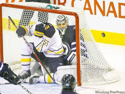 The Sabres' Jochen Hecht covers up after finding himself the target of his own team inside the Jets net with goalie Ondrej Pavelec in second-period action Thursday.