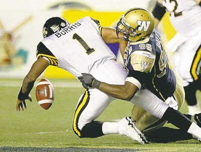 Winnipeg�s  Alex Hall takes down  Hamilton�s Henry Burris in the fourth quarter.