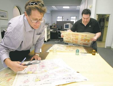 Reporter Bruce Owen peruses maps while Martin Comeau, archivist with Winnipeg's city clerk's department, pulls out some of the turn-of the-century maps the Winnipeg Fire Department once used for keeping track of building types.
