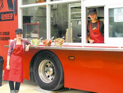 Jamie Poirier and Max Steinwachs help out in Red Ember's mobile kitchen.
