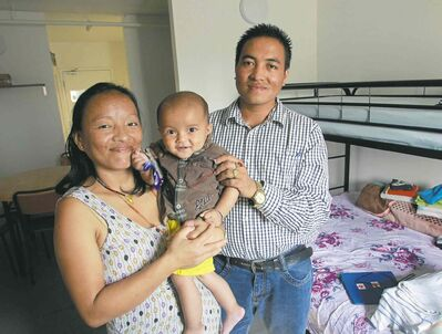 wayne glowacki / winnipeg free pressLaxman Bhujel with his wife, Sukhamina Rai and Ryan, one of their two young  children, in their small bachelor suite in Welcome Place.