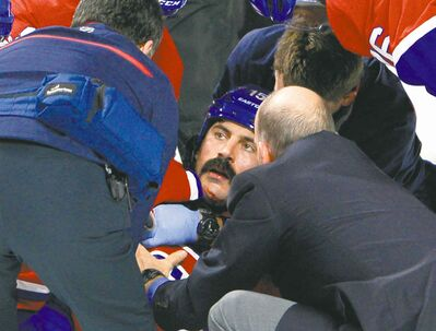 Canadiens enforcer George Parros is treated by medical staff after falling face first onto the ice during a fight with Maple Leafs enforcer Colton Orr on Tuesday.