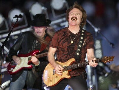 Doobie Brothers members Tom Johnston, right, and Patrick Simmons, back left, perform during halftime at the Orange Bowl NCAA college football game in Miami, Thursday, Jan. 1, 2009.