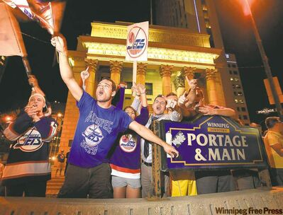 Hockey fans celebrate at Portage and Main last Thursday after a premature report of the NHL's return. A celebration of an actual announcement will dwarf this bash.