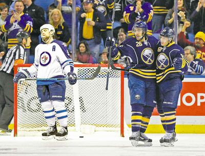 Sabres forward Matt Moulson (26) celebrates his power-play goal in the third period with teammate Tyler Ennis while Jets blue-liner Mark Stuart can't bear to look.