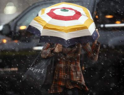 A woman uses an umbrella to shield herself from light rain and snow falling this morning.