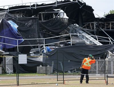 Workers install a security fence in front of the Ottawa Bluesfest main stage which collapsed during a storm in Ottawa, Monday July 18, 2011. The executive director of the Ottawa Bluesfest says he's looking at closer liaison with the weather office in the wake of a violent summer gale which toppled the main stage at the festival on Sunday. THE CANADIAN PRESS/Adrian Wyld
