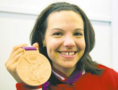 Ryan Remiorz / The Canadian PressQuebec�s Christine Girard shows off her bronze medal in the women�s 63-kg weightlifting final in London on Tuesday.