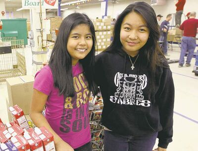 photos by JOE BRYKSA / WINNIPEG FREE PRESS Denise Estacio (in pink) and Icah Navidad join classmates from Cecil Rhodes School in packing hampers on Thursday.