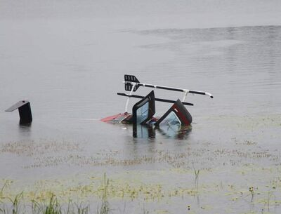A helicopter lies on its side partially submerged after making an emergency landing in Kississing Lake near Sherridon in northern Manitoba on Sunday.