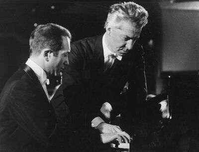 Pianist Alexis Weissenberg. left, and Austrian conductor Herbert von Karajan, as they go over a part at the grand piano in West Berlin.