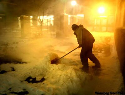 Bela Castro shovels the sidewalk outside the Free Press building Friday morning after the season's first major dump of snow.