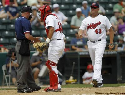 Goldeyes catcher Luis Alen argues with home plate umpire Lance Schoenwald as Fish manager Rick Forney prepares to enter the fray.